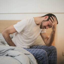 Man sitting on bed tired after waking up early.