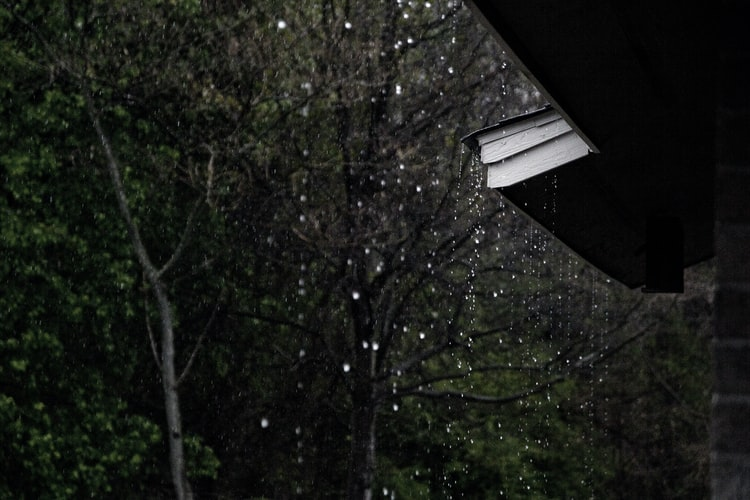 Rain falling from a house roof and gutter.
