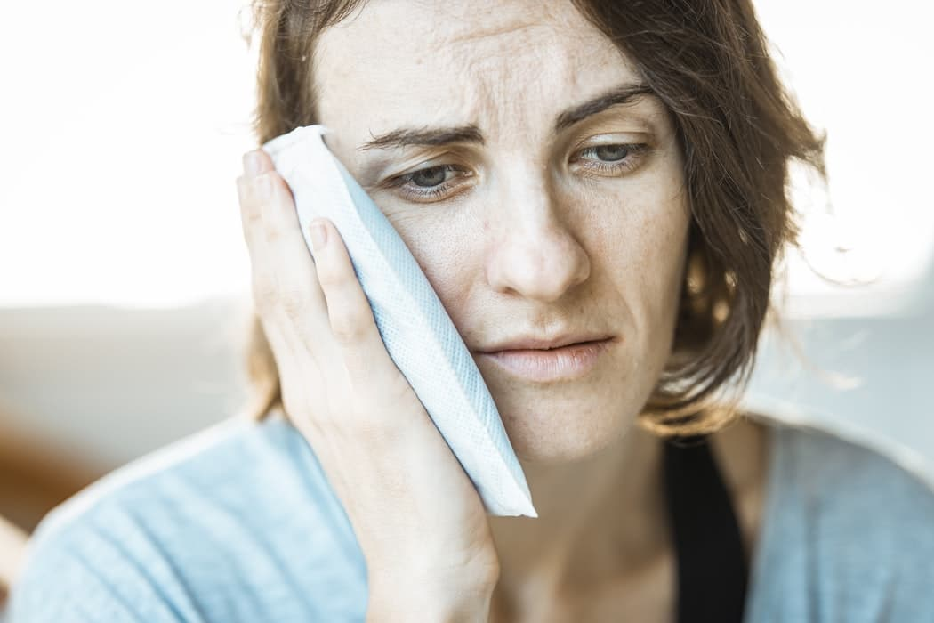 Woman holding an ice pack up to her ear.